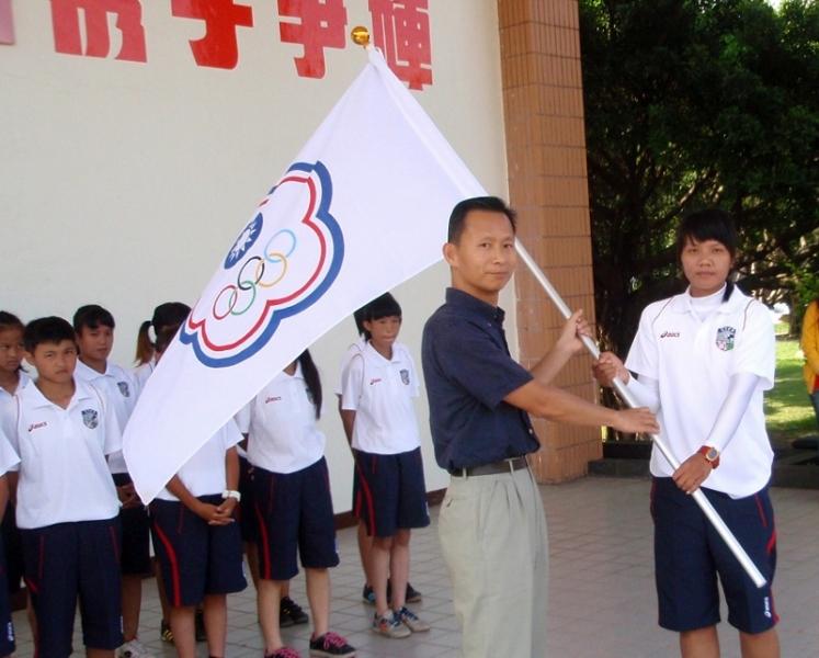 中華足球協會秘書長王筱薰(左)授旗予總教練郭慈慧。